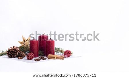 Christmas Candles on white, Weihnachtsdekoration auf weissem Hintergrund  Rote, brennende Kerzen, Zimtstangen und Zweige Stock foto ©
