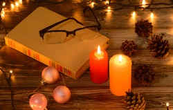 Christmas candles with boock and glasses pine cones christmas lights on wooden background. Christmas background