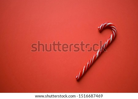 Christmas candy cane candy cane on bright red background, minimalism, space for your text #1516687469