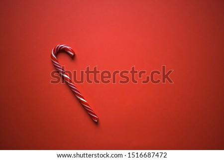 Christmas candy cane candy cane on bright red background, minimalism, space for your text #1516687472