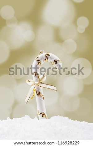 Christmas candy cane on the snow with bow and golden christmas light background