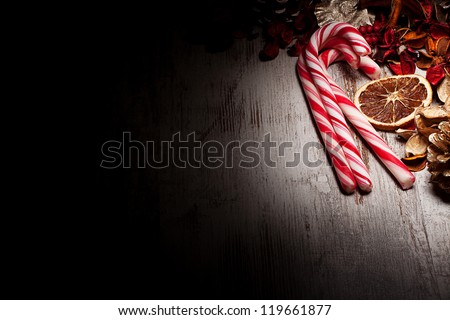 Christmas candy canes and decorations over wooden background