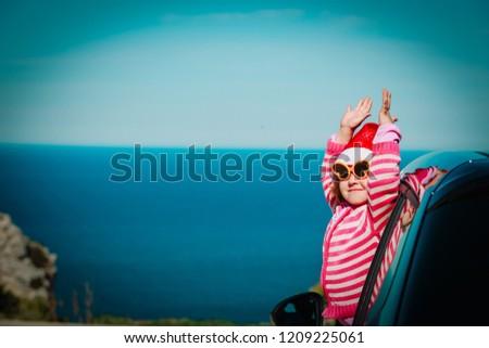 christmas car travel- happy little girl loves travel in winter #1209225061
