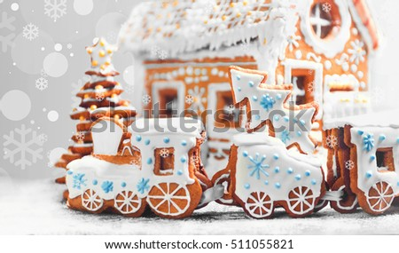 Christmas card. Assorted Christmas gingerbread cookies. Christmas gingerbread village, house, train, tree. Christmas New Year\'s background with snowflakes. Christmas food gingerbread house, train