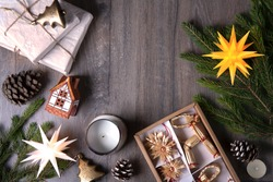 Christmas card. Christmas tree branch, German stars, box with straw stars and deer, ceramic house, pine cones, candle and gifts on a wooden background. View top