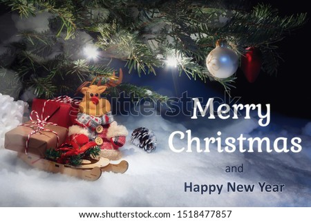 Christmas card - Christmas tree in the snow, gifts, toy deer and the inscription Merry Christmas and Happy New Year