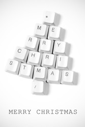 Christmas card - Christmas tree made of computer keys, white background with vignette