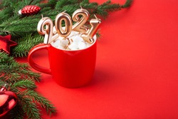 Christmas card, cocoa with marshmallows in a red mug, spruce branches on a red background, candles 2021