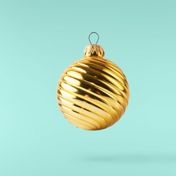 Christmas card conception. Christmas gold bauble falling in the air on turquoise background. Levitation concept. High resolution image
