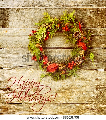"Christmas card design featuring  a home made christmas wreath with natural decorations hanging on a rustic wooden wall with text ""Merry Christmas."""