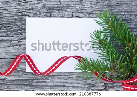Christmas card: empty paper form with fir-tree branches and red tape on old wooden background