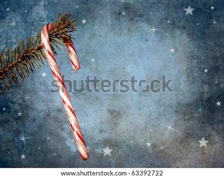Christmas card featuring a candy cane hanging from a pine branch with whimsical designs and copy space. Grunge textured. - stock photo