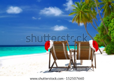 Christmas card or background - two sunloungers with Santa hats standing on beautiful tropical beach with palm trees, white sand and turquoise water on Maldives. Concept of perfect vacation.
