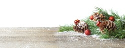 Christmas card. Pine cone and green branch on wooden table with snow, copy space for text, isolated on white background