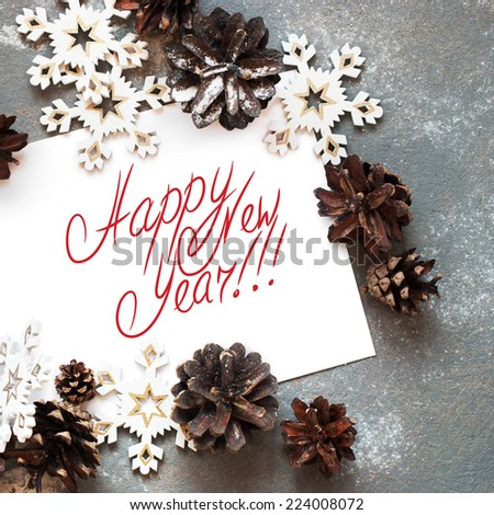 Christmas Card with Decoration Snowflakes  and Pine cones,  Message Happy New Year on the letter, isolated on white