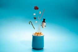 Christmas card with hot chocolate with marshmallows and cinnamon on blue background.Shot of hot drink in freeze motion,flying candy cannes,apples,anise star and snowman.Drink levitation.