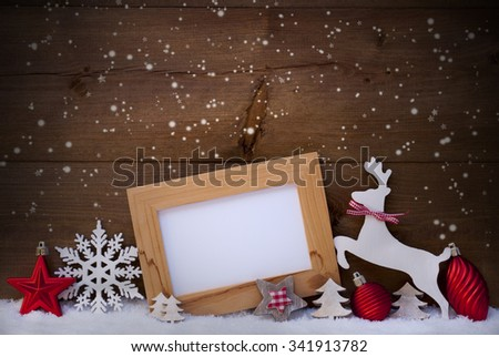 Christmas Card With Picture Frame On Snow. Copy Space For Advertisement. Red Christmas Decoration Like Christmas Ball, Snowflakes, Tree, Star And Reindeer. Wooden And Vintage Background