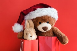 Christmas card with Teddy Bear and bunny With gift and holiday decoration. Hare and bear in red gift bags.