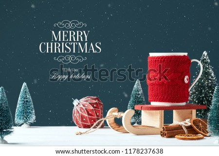 Christmas card with the inscription Merry Christmas. White mug with cocoa in red knitted clothes on Santa Claus sleigh dark background toy tree, red ball, cinnamon sticks a slice. Snowing. Front view