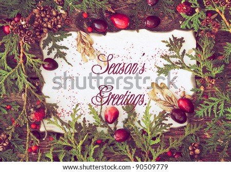 "Christmas card with with cedar sprigs, berries and other natural decorations framing an old paper center with text ""Season's Greetings!""."