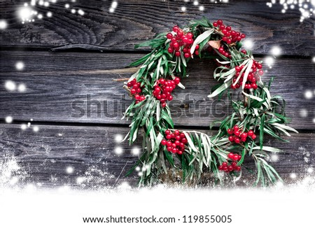Christmas card with wreath,red berry on a rustic wooden wall with copy space and  snow/ holidays background