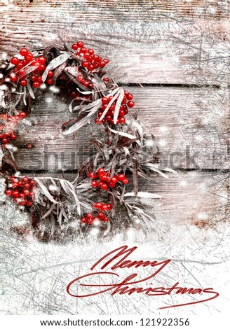 Christmas card with wreath with natural decorations hanging on a rustic wooden wall with copy space with a snow/holidays background