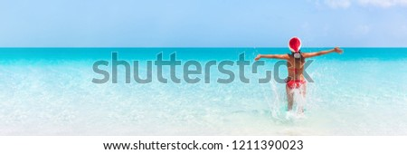 Christmas Caribbean beach tropical Santa Claus woman Happy swimming in blue ocean water panorama banner. Bikini girl with pen arms freedom carefree. Travel vacation holidays under the tropical sun.