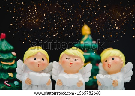 Christmas caroling or Carolers singing on black background.Angel group singing carol song on celebration of christmas season in winter time.Chorus singing, Worship, and Sing a song in winter concept.