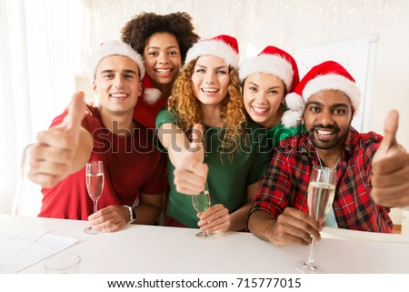christmas, celebration and holidays concept - happy team in santa hats with non-alcoholic sparkling wine at corporate office party and showing thumbs up #715777015