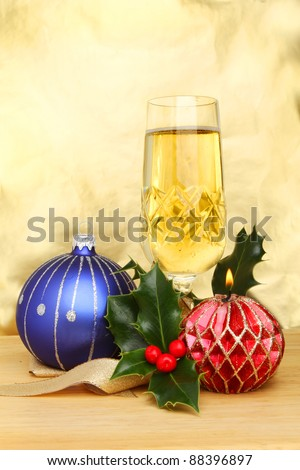 Christmas cheer, a glass of champagne with a blue bauble, decorative burning candle, gold ribbon and a sprig of holly against a gold background
