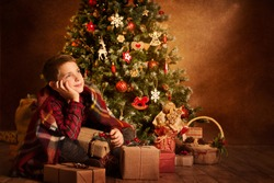 Christmas Child Dreaming under Xmas Tree, Happy Boy Kid with New Year Presents Gifts