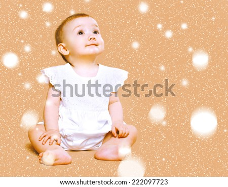 Christmas, children and people concept - cute little baby dreams looking on the snowflakes