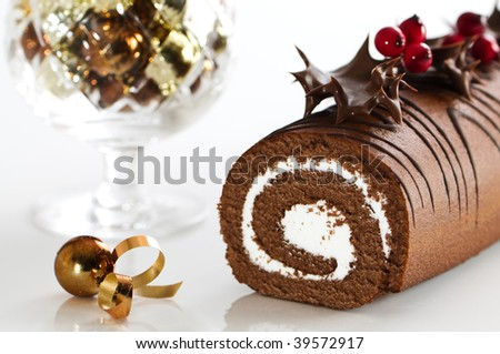 Christmas chocolate yule log cake decorated with chocolate coated holly and berries