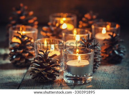 Christmas Christmas card with glowing small candle and fir cones on old wooden background, dark toned image in country style, selective focus