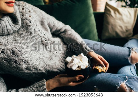 Christmas, cold autumn or winter day. Warming mood. Woman drinking warm cocoa with marshmallows. Lazy weekend in knitted sweater on the couch. Cozy scene, hygge concept