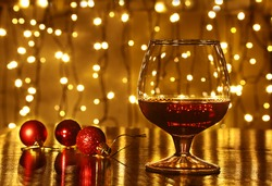 Christmas colorful balls and glass cognac or whiskey with defocused lights