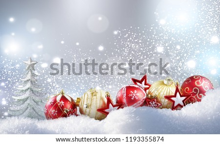Christmas colorful layout. Christmas golden balls, red stars and Christmas tree on snow in winter snowdrift on silvery sparkling background with falling snow and copy space. - Shutterstock ID 1193355874