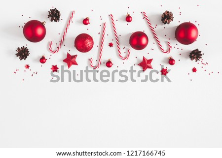 Christmas composition. Border made of red decorations on pastel gray background. Christmas, winter, new year concept. Flat lay, top view, copy space #1217166745