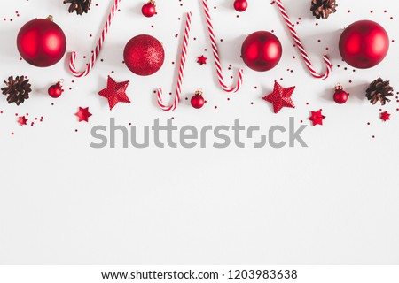 Christmas composition. Border made of red decorations on white background. Christmas, winter, new year concept. Flat lay, top view, copy space #1203983638