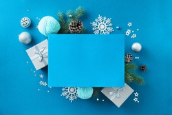 Christmas composition. Christmas decor, gift boxes, pine cones, branches and confetti stars on blue background. Flat lay, top view, copy space.