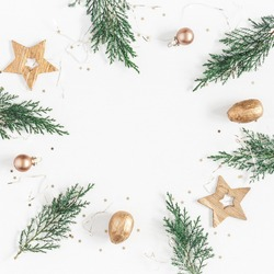 Christmas composition. Christmas frame made of conifer branches, balls, golden decorations on white background. Flat lay, top view, copy space, square.