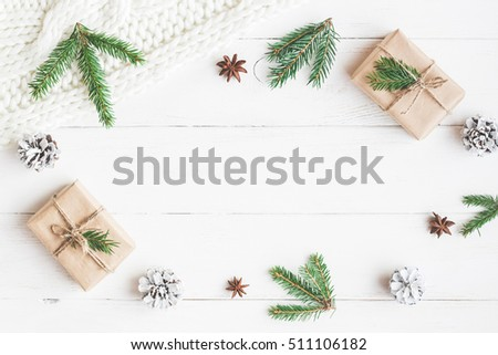 Christmas composition. Christmas gift, knitted blanket, pine cones, fir branches on wooden white background. Flat lay, top view - Shutterstock ID 511106182
