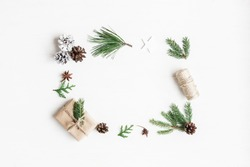 Christmas composition. Christmas gift, pine cones, fir tree branches on white background. Top view, flat lay, copy space.