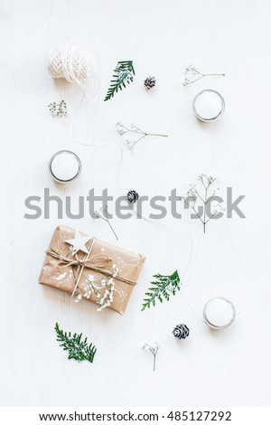 Christmas composition. Christmas gift, pine cones, thuja branches, gypsophila flowers. Top view, flat lay