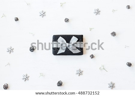 Christmas composition. Christmas gift, snowflakes, pine cones and gypsophila flowers. Top view, flat lay