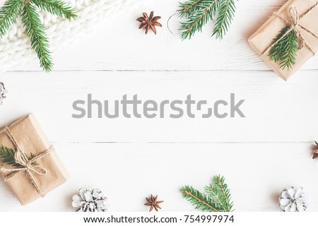 Christmas composition. Christmas gifts, fir tree branches, knitted blanket on white wooden background. Flat lay, top view, copy space.
