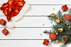 Christmas composition. Christmas greeting card with fir tree branches, Santa Claus hat, decorations on a white wooden background. mock up. Copy space. flat lay.