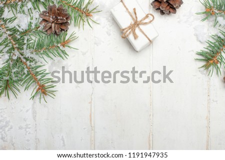 Christmas composition. Christmas present, pine cones, spruce branches on a wooden white background. Flat lay, top view, space for copy #1191947935