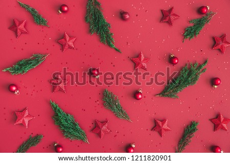 Christmas composition. Christmas red decorations, fir tree branches on red background. Flat lay, top view