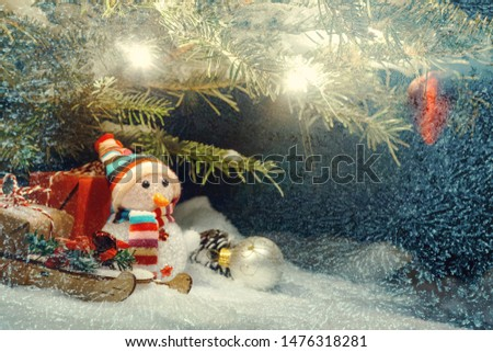 Christmas composition - Christmas tree in the snow, gifts, toy snowman and the inscription Merry Christmas and Happy New Year, copy space, place for text